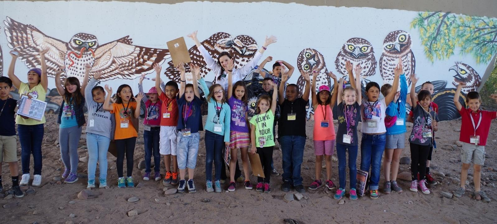 A line of students pose in front of a Burrowing Owl mural under a bridge.