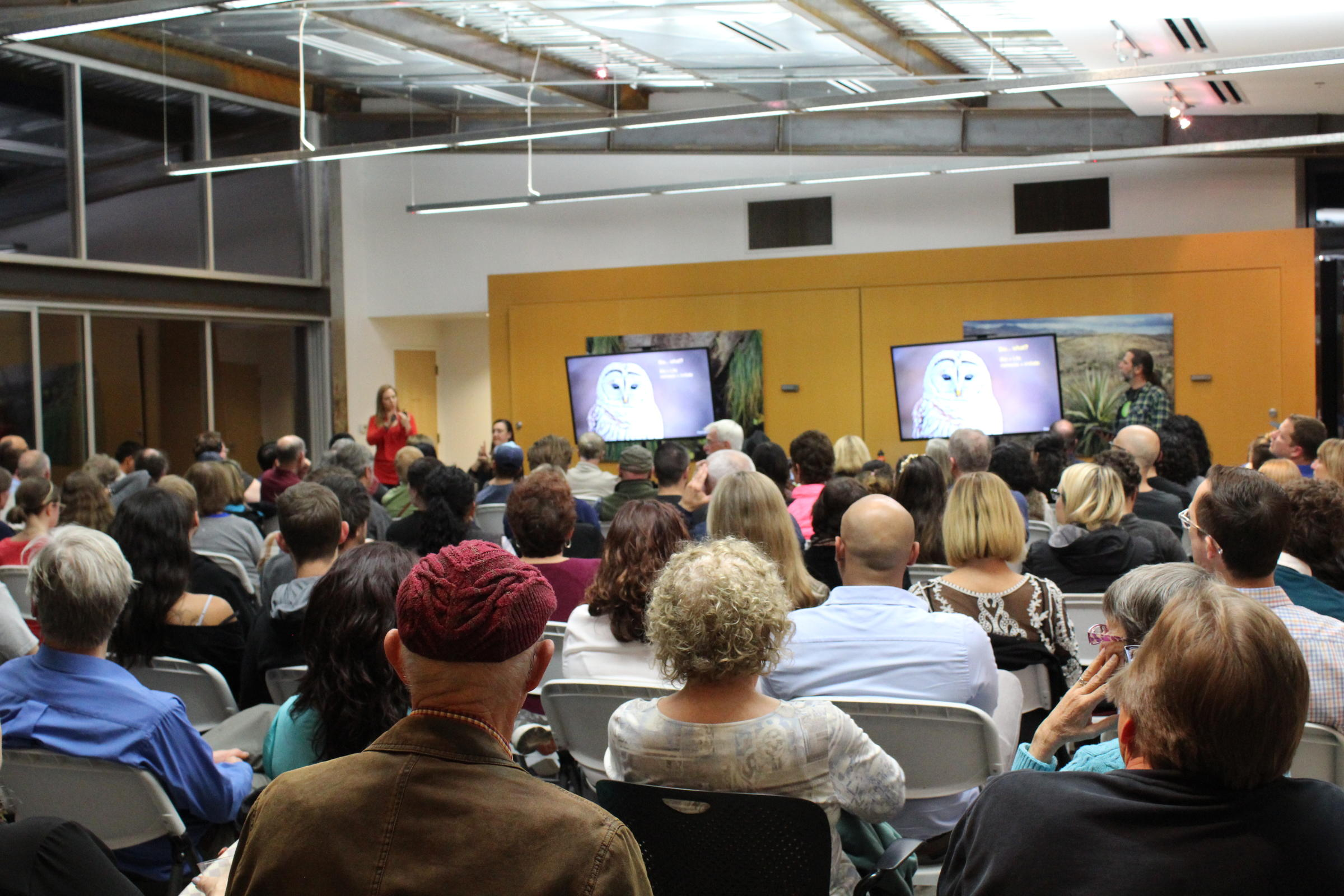 A crowd of people listen to a lecture on biomimicry while seeing images of inspirations from nature, like a owl, on a TV screen.
