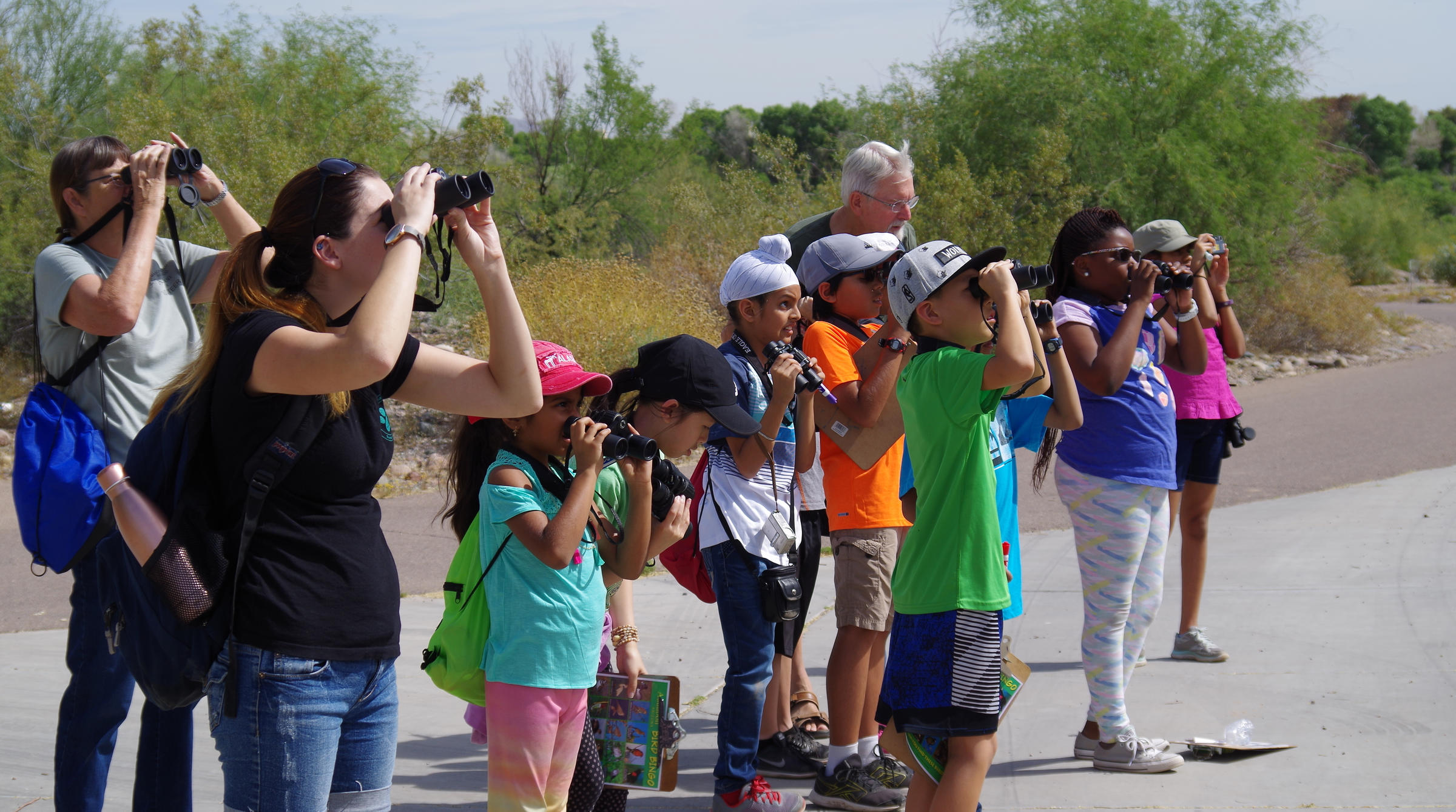 A group of students with chaperones look at a bird with binoculars during a field trip.